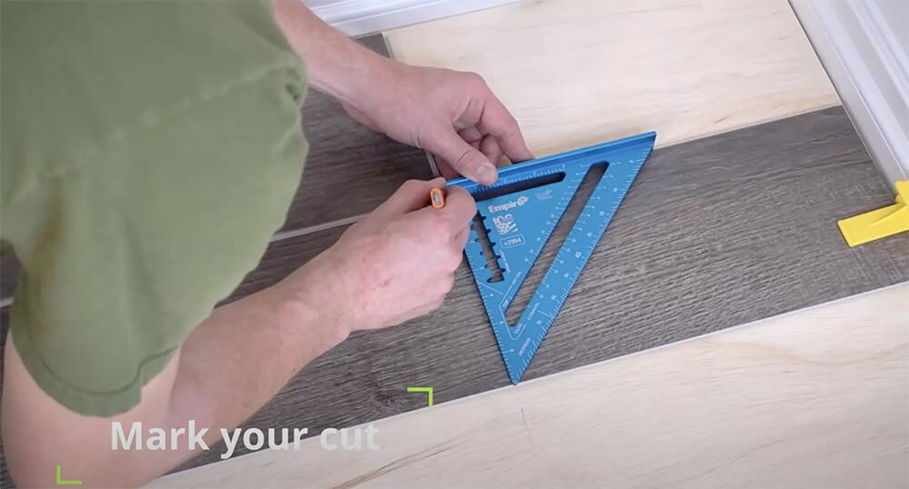 Person marking a cut line on a luxury vinyl plank