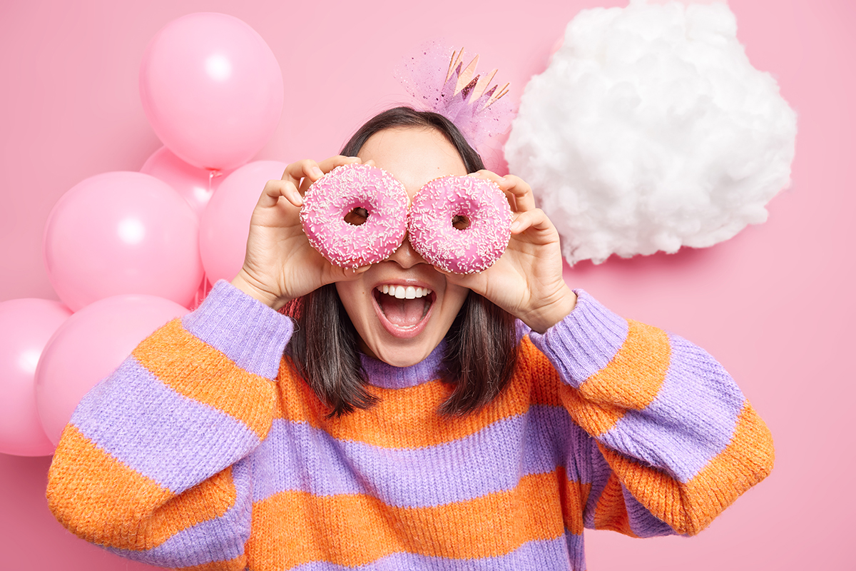 Young woman looking through pink donuts with party balloons in the background