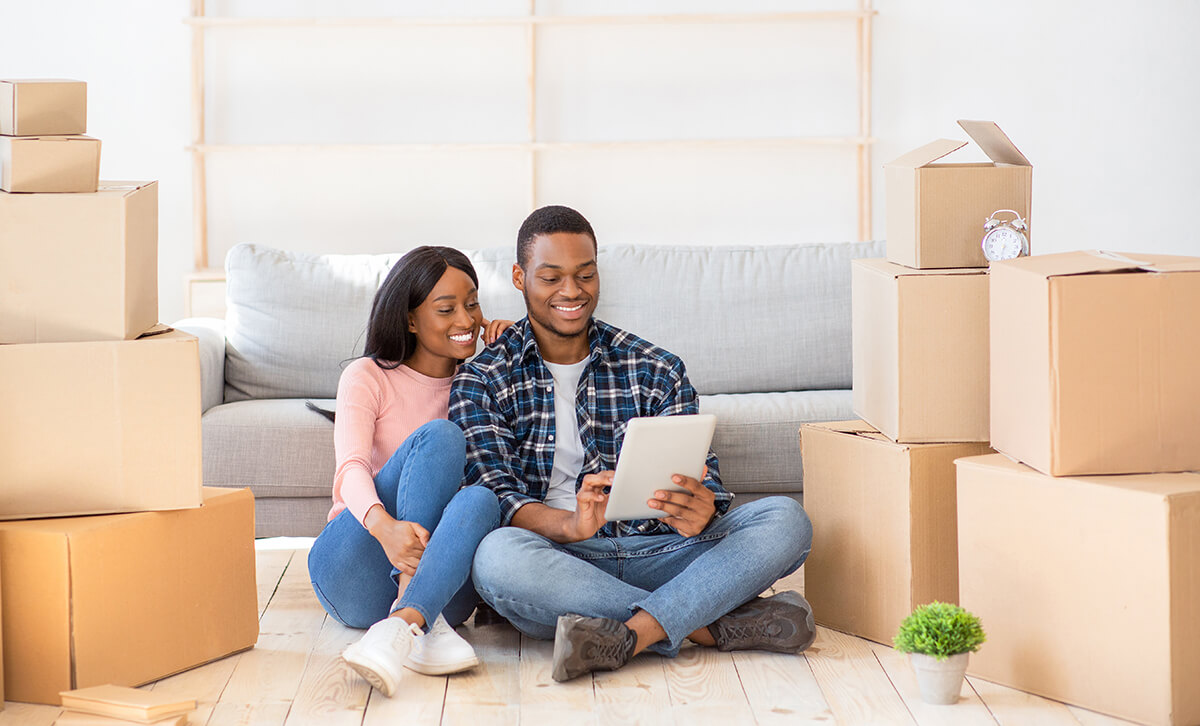 Millennial couple sitting between boxes in their new apartment