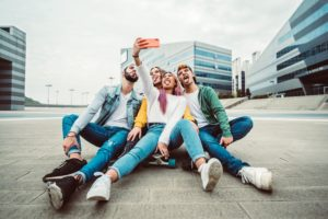Group of young people taking selfies in front of apartments