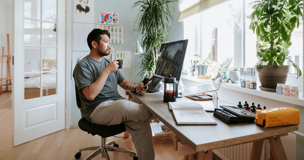 Man drinking coffee while working remotely in his condo